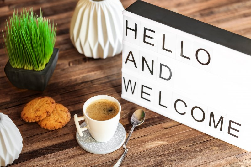 Hello and welcome sign on table with coffee and plant